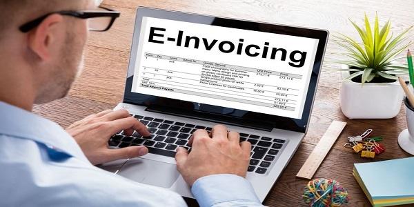 Businessman Preparing E-Invoicing Bill On Laptop At Desk