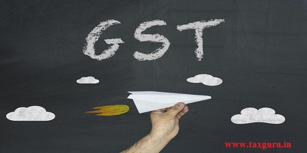 GST - Goods and Services Tax concept. Male hand holding paper aircraft on blackboard with inscription GST