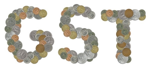 GST word with stack of coins on white background