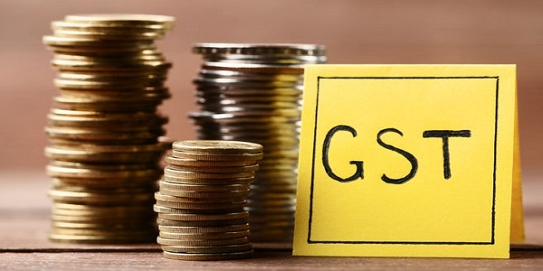 Inscription GST Goods and Services Tax on paper with stack of coins