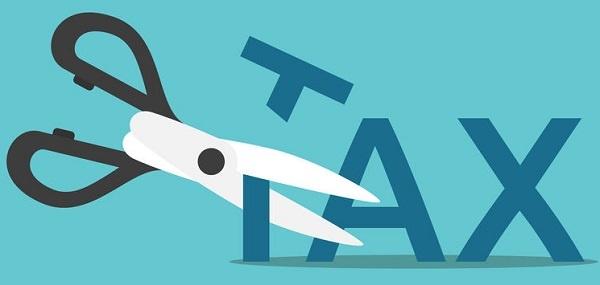 Tax Deduction- Tax Saving Scissors cutting word tax on blue background