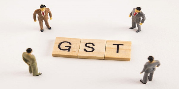 Miniature figures businessman : meeting on gst letters by wooden block word on white paper background, gst is acronym from word Goods and Services Tax.