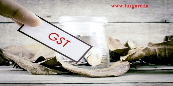Cropped finger holding white label with black frame with word GST Goods and Services Tax. Background with coin in glass jar surrounded by dry leaves and wood