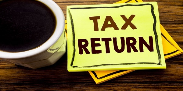 Handwritten text showing Tax Return. Business concept for Taxation Refund written on sticky note paper on wooden wood background with coffee cup