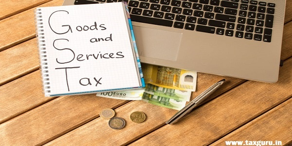 Goods and Services Tax GST- Laptop, pen, coins, banknotes on wood background