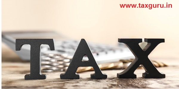 Word TAX on wooden table and calculator with coins