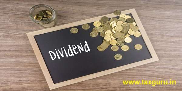 Gold coins in glass jar with Dividend words on chalkboard