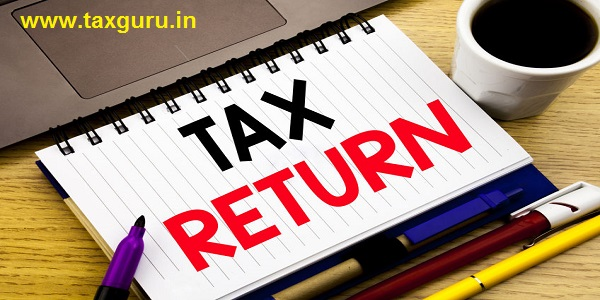 Tax Return written on notebook book with laptop coffee & wooden background