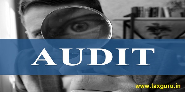 Audit concept. Auditor with a magnifying glass in the office.