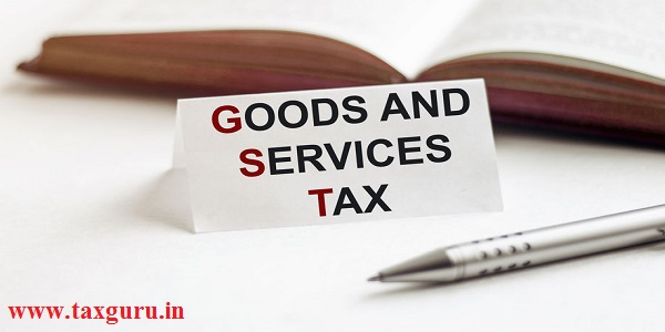 piece of paper with text GST GOODS AND SERVICES TAX on the background of books, pens, on a white background
