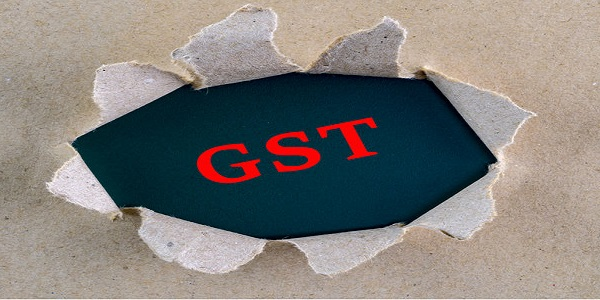Torn brown rough textured paper with GST Goods and Services Tax word at background surface.