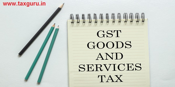 two green one black pencil with text GST GOODS AND SERVICES TAX in the notebook on the white background