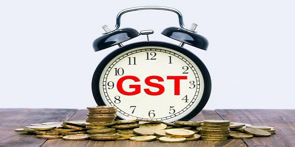 Written word GST Goods and Services Tax on a clock with gold coins on top of a wooden t