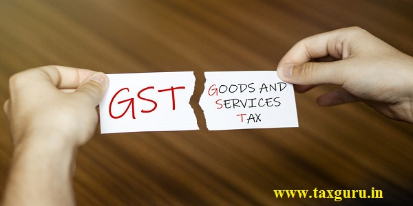 torn paper with text GST GOODS AND SERVICES TAX in male hands on wood background