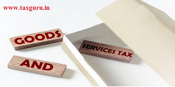 wooden blocks with text GST GOODS AND SERVICES TAX in a box on a white background