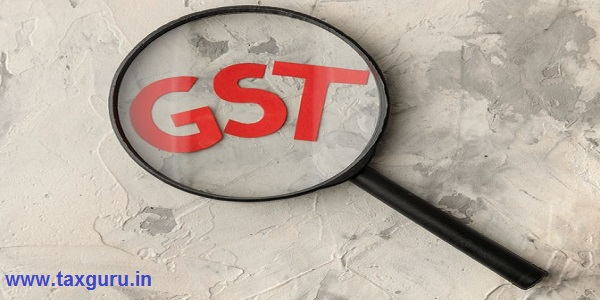 The word GST under a magnifying glass on a light concrete background. view from above
