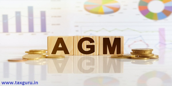 AGM the word on wooden cubes, cubes stand on a reflective surface, in the background is a business diagram.
