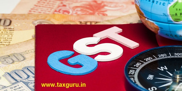 Closeup of GST words with globe, compass and Rupee notes
