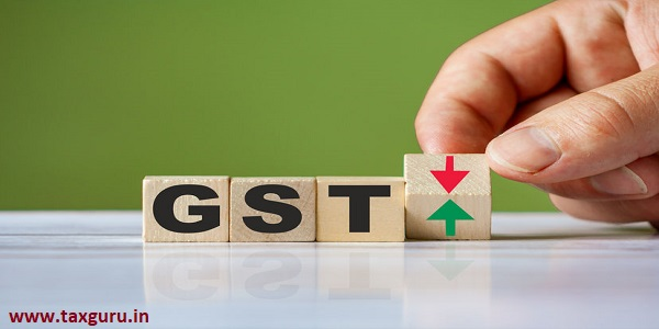 Hand turn wooden block with red green arrow as change concept of GST Goods and Services Tax