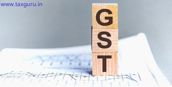 Wooden block with words GST - acronim GST - Goods and Services Tax. GST wooden blocks on the paper grey background