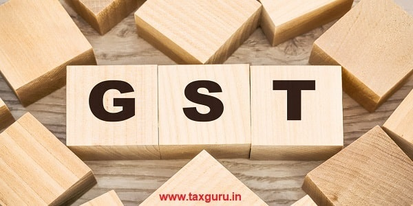 Black letters GST (Goods and Service Tax) on small wooden blocks