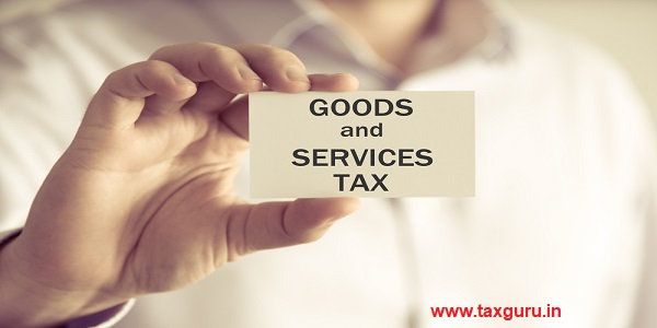 Closeup on businessman holding a card with text GST GOODS AND SERVICES TAX
