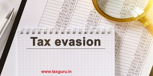 On the table are financial reports, a pen, a magnifying glass and a notebook with the inscription - Tax evasion
