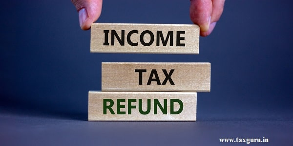 Wooden blocks form the words 'Income tax refund' on grey background