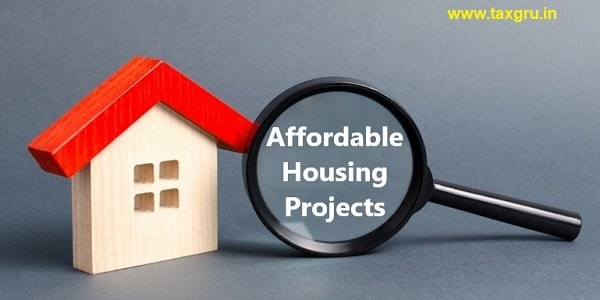 Wooden house and Affordable Housing Projects  with magnifying glass on a gray background