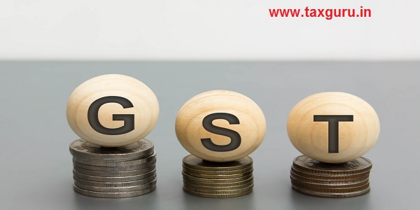 Wooden letters GST and money coin stack on gray table background
