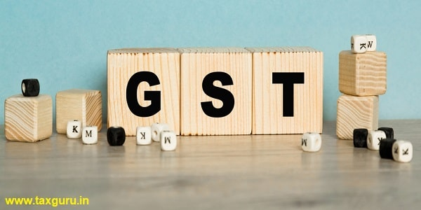 Word GST (Goods and Service Tax) are written on a wooden cubes structure
