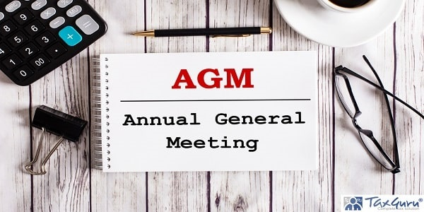 AGM Annual General Meeting is written in a white notepad near a calculator, coffee, glasses and a pen