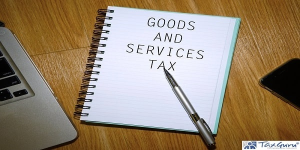 GST Goods And Services Tax - Notebook with laptop and smartphone on wooden table