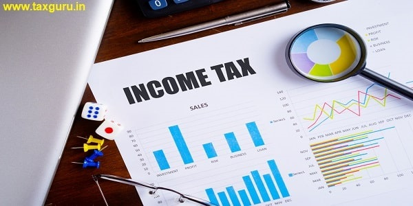 Income Tax text on paper sheet with magnifying glass on chart, dice, spectacles, pen, laptop and blue and yellow push pin on wooden table