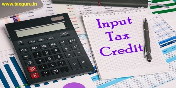Input Tax Credit - Calculator and an empty Notepad page on the office Desk with financial indicators and charts
