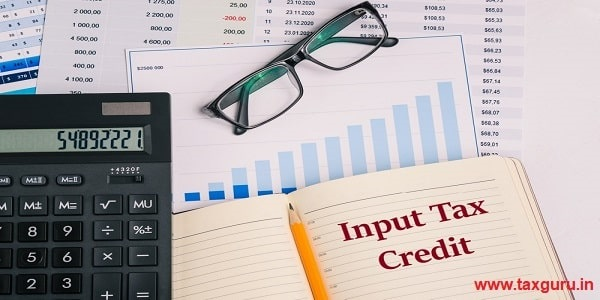 Input Tax Credit - Workplace with financial papers, charts, accounting documents, a large calculator, an open notebook and glasses