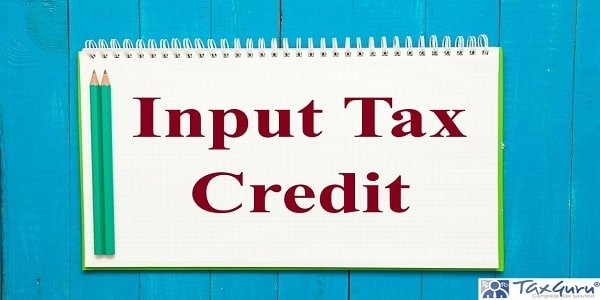 Input Tax Credit - open notebook with pencil on a blue wooden background