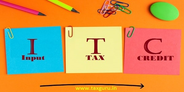Input Tax Credit words on notes pasted on orange background with a big arrow and office supplies