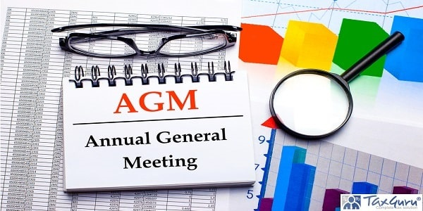 On the desktop are glasses, a magnifying glass, color charts and a white notebook with the text AGM Annual General Meeting