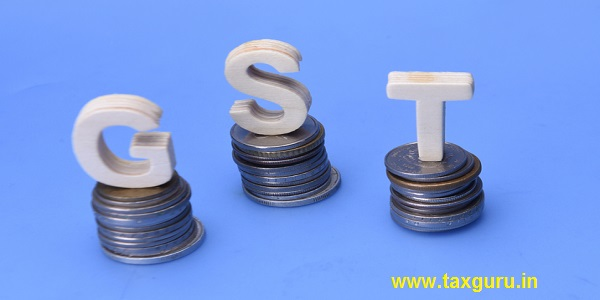 The word/abbreviation GST (Goods and services tax) on stack of coins over blue background