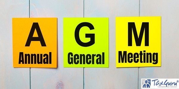 Three colored stickers with the text AGM Annual General Meeting on a light blue wooden background