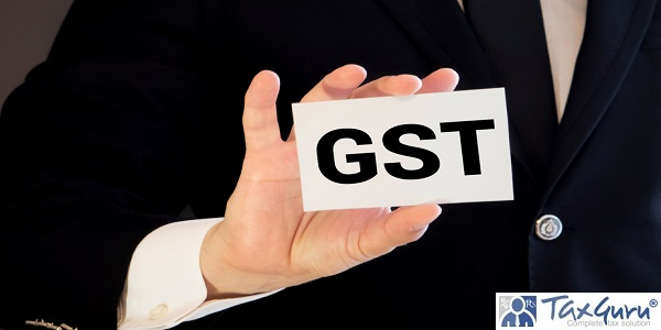 Closeup on businessman holding a card with GST GOODS AND SERVICES TAX message