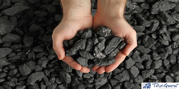 Man holding coal in hands over pile, top view