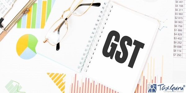Text GST on white notepad, glasses, graphs and diagrams