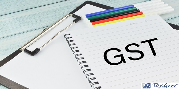 Top angle view of pen colors, paper holding file and notebook written with text GST on a wooden background
