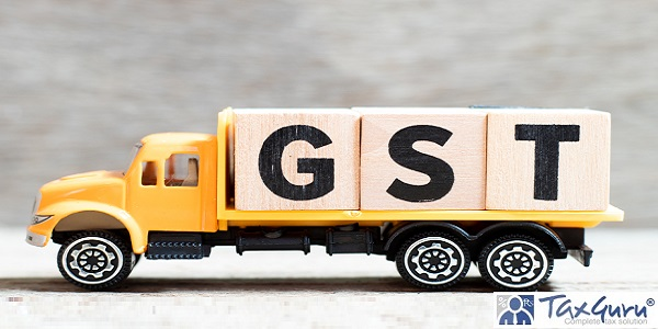 Truck hold letter block in word GST (Abbreviation of Goods and Service Tax) on wood background
